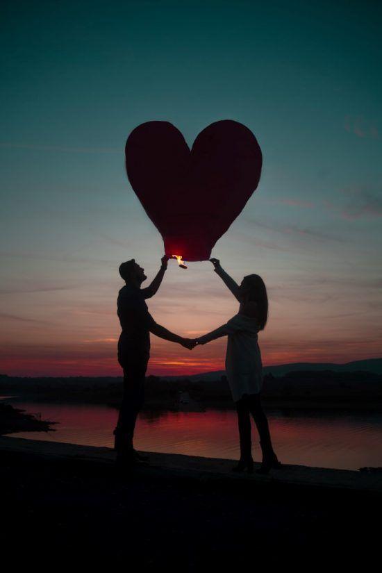 eine Frau und ein Mann halten einen Herzballon in die Luft