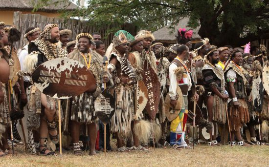 Zulu tribe standing in a line in Rhino Africa's Complete Guide