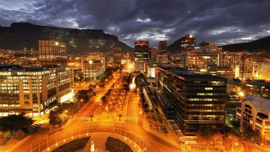 Adderly Street in Kapstadt bei Nacht: eine große beleuchtete Straße und viele Hochhäuser