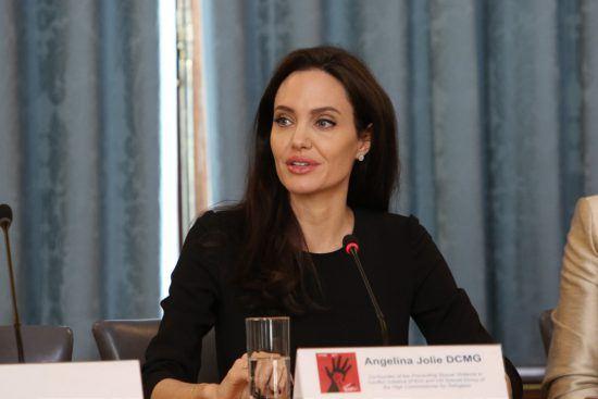 eine Frau sitzt vor einem Mikrofon, vor ihr steht ein Glas Wasser