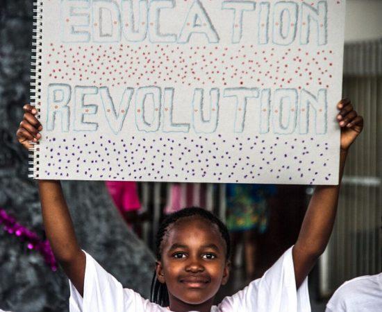 """Un élève de Good Work Foundation portant une pancarte """"Education Revolution""""."""