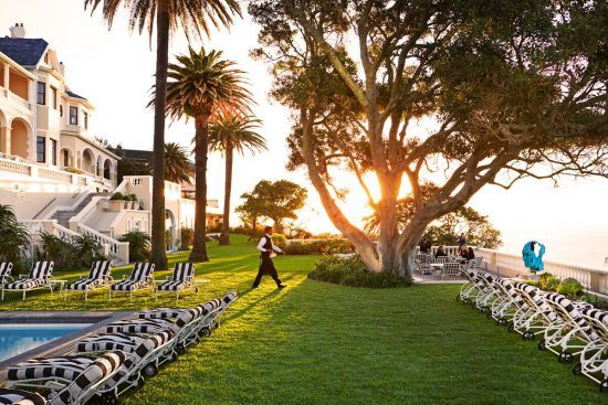 A waiter crosses the lawn in Ellerman House's grounds to serve a guest.