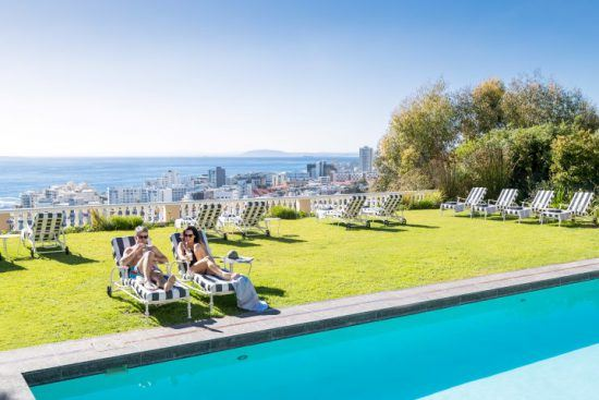 Paar relaxt in Sonnenliegen am Pool des Ellerman House