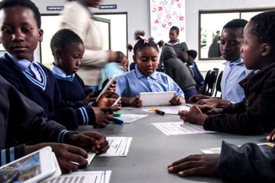 Kinder in blauer Schuluniform lernen mit Tablets am Justicia Campus der Good Work Foundation