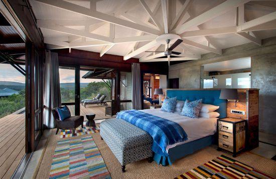 Ein Schlafzimmer mit Bett und Balkon nach draussen in den Wald