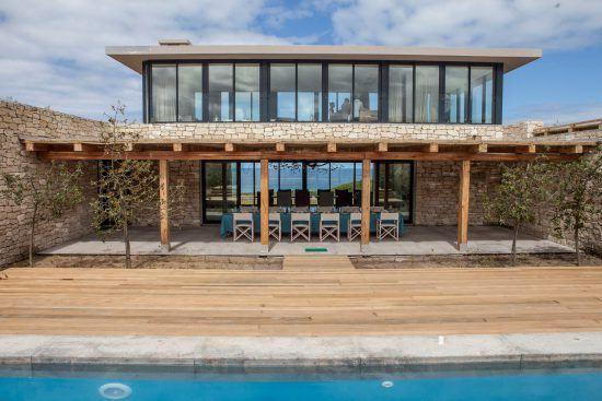ein Pool, dahinter eine große Suite und ein großer Tisch