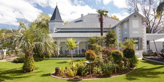 ein Gebäude im Kolonialstil, runherum ein grüner Garten
