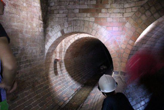 Ein Tunnel in Kapstadt, eine Person mit Helm schaut hinein