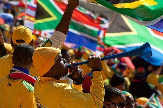 Südafrikanischer Fußballfan trötet mit einer Vuvuzela in einem gefüllten Stadion - Fußball-Weltmeisterschaft in Südafrika