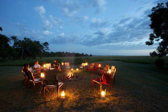 Ein Lagerfeuer und einige Sessel und Personen im Dunkeln in Kenia