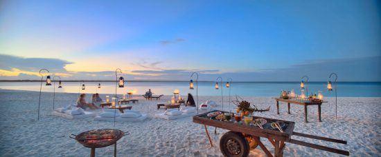auf einem Strand sind Tische und Lampen aufgestellt