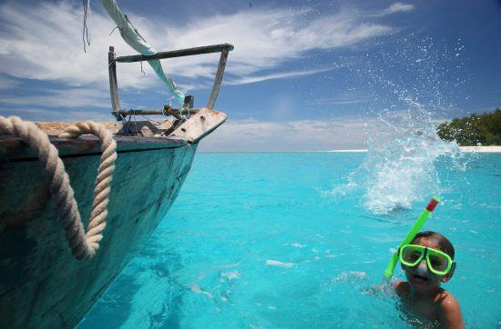 ein Kind mit Taucherbrille im Meer neben einem Boot in Sansibar