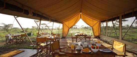 unter einem Zelt sind Tische und mit Frühstück darau, dahinter die Savanne