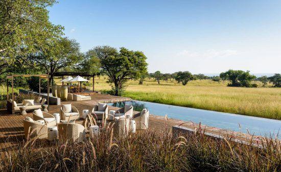 Ein Pool und einige Tische und Sesseln, dahinter grünes Gras in Tansania