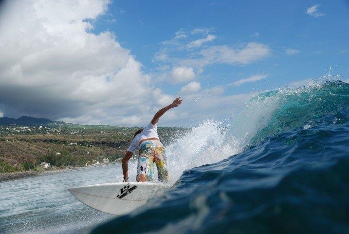 Ein Surfer reitet eine Welle vor der Küste von La Réunion