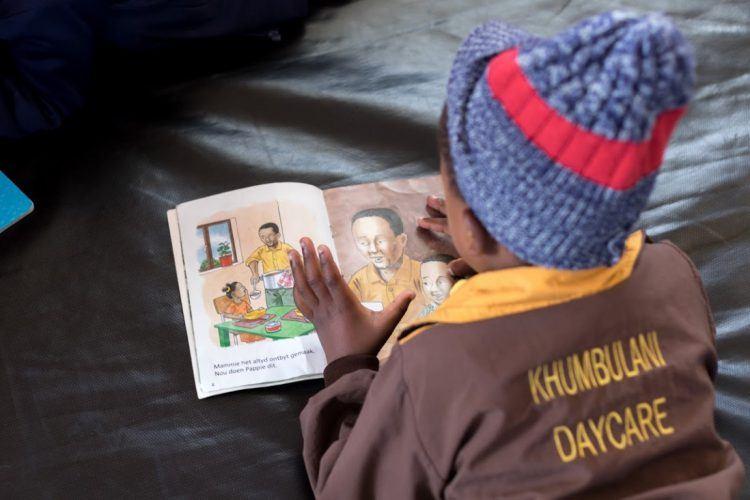 Enfant apprenant à lire au centre de Khumbulani au Cap