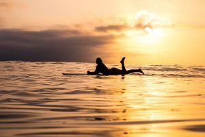 Una surfista se relaja en su tabla al atardecer