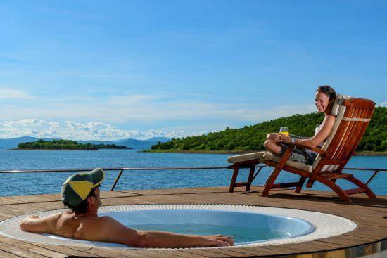 Mann erfrischt sich an Bord im Pool und seine Frau sonnt sich