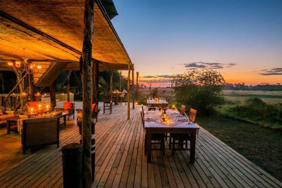 The open-plan dining area at The Hide leads directly into the picturesque savannah
