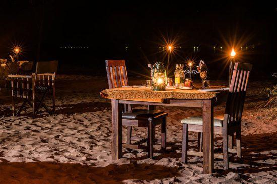 Ein Tisch im Kerzenschein am Strand vorm Changa Safari Camp