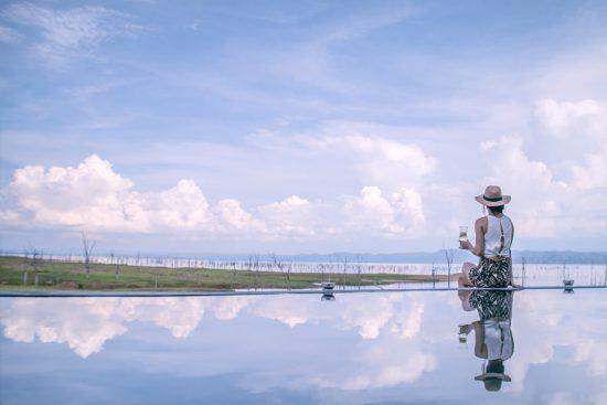 Eine Frau sitzt am Beckenrand eines Infinity-Pools und blickt auf den Lake Kariba