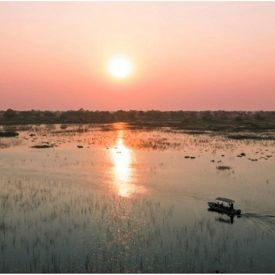 Eine romantische Bootsfahrt bei Sonnengang im Okavango Delta in Botswana