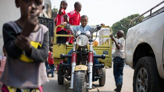 Un enfant sur une grande moto d'adulte dans les rues de Brazaville au Congo.