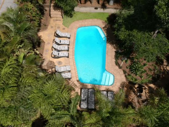 Der Swimmingpool der Lidiko Lodge im tropischen Garten von oben