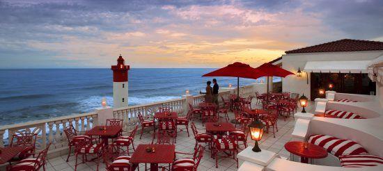 Blick von der Terrasse des Oyster Box Hotel auf einen romantischen Sonnenuntergang sowie einen Leuchtturm