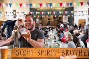 Mann zapft Bier (Craft Beer) in Südafrika während er in einem geschmückten Festzelt sthet