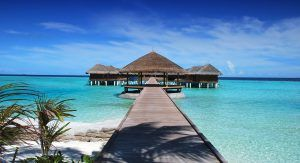 Wooden walkway leads to elevated huts over the Indian Ocean in Maldives