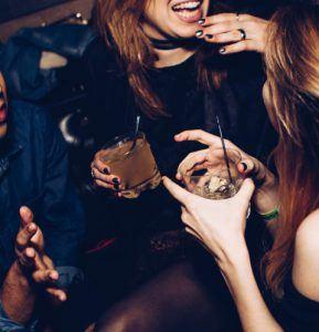 Zwei Frauen mit Drinks in der Hand feiern Silvester