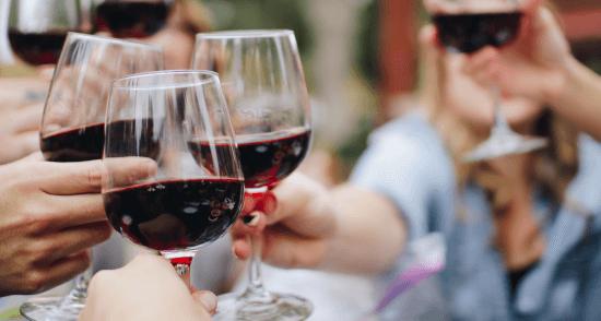 Personen stoßen mit Rotwein an