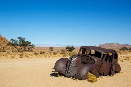 Ein altes, ausgebranntes Auto im Ghost Valley in Namibia