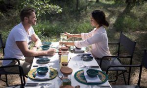 A couple is enjoying their breakfast in the South African bush at Silvan Safari