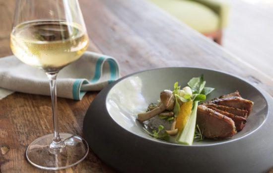 Kunstvoll angerichtetes Essen nebem einem Glas Weißwein