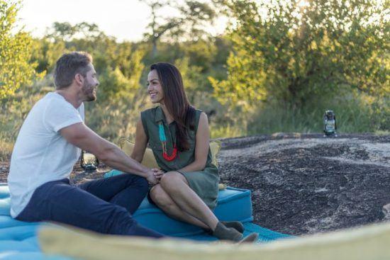 Flitterwochen im Sabi Sand Game Reserve: Ein Paar sitzt beim Sundowner im südafrikanischen Busch