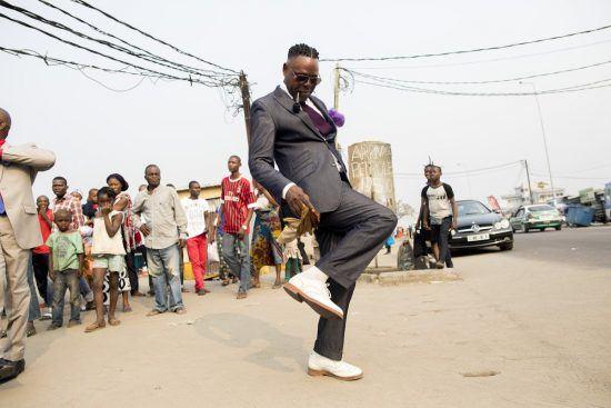 Ein Sapeur im grauen Anzug tanzt in den Straßen von Brazzaville