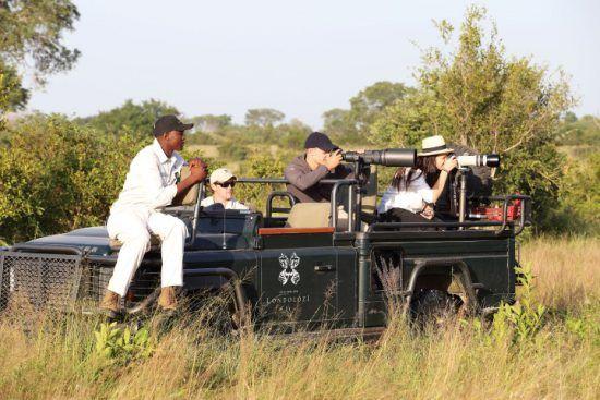 Aktivitäten bei Londolozi: Safari-Urlauber machen in einem speziell für Foto-Safaris gebauten Fahrzeug Fotos