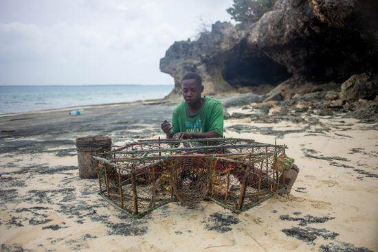Ein Angler flickt am Strand von Sansibar seine Netze