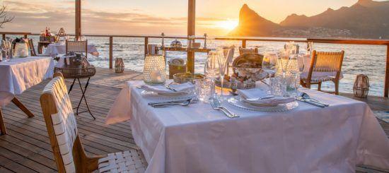 Gedeckter Tisch auf der Terrasse von Tintswalo Atlantic im Licht der untergehenden Sonne