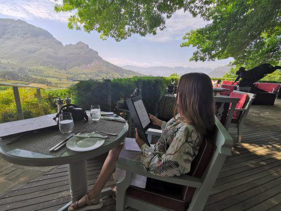 Katharina Riebesel liest auf der Terrasse des Delaire Graff Restaurants die Speisekarte