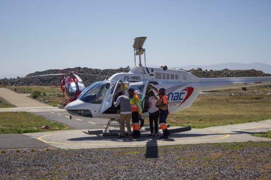 Rhino-Africa-Mitarbeiter steigen in einen Helikopter von NAC