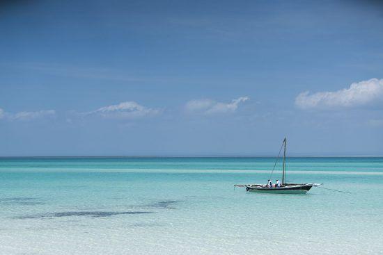 Beste Reisezeit für Mosambik: Boot im seichten, türkisblauen Wasser vor Mosambik