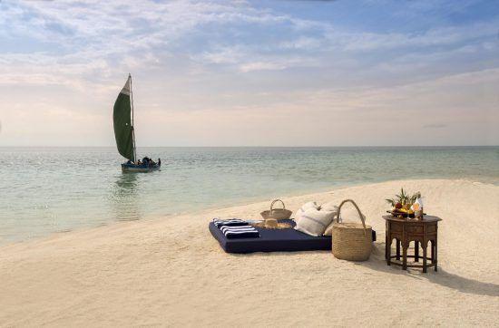 Picknick am goldenen Strand mit Segelboot im Hintergrund