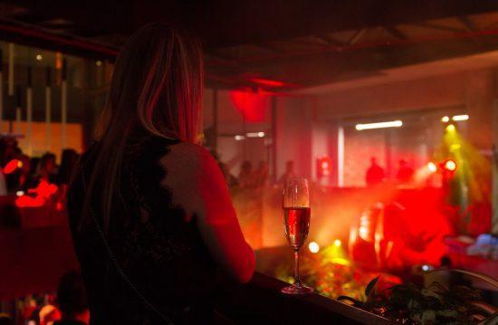 Silvester 2019/20 in Südafrika: Frau steht neben einem Glas Champagner und schaut bei einer Show zu
