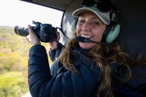 Bianca Johnstone taking a photo on a helicopter flight