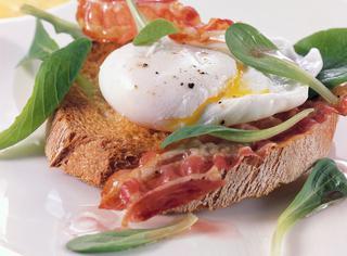 Uovo in camicia sul crostone di pane con la pancetta