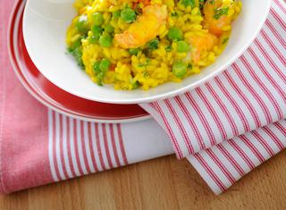Risotto al curry con piselli e scampi