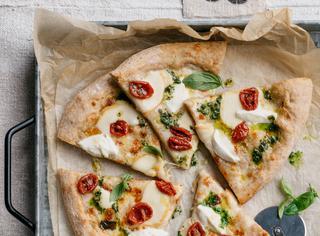 Pizza multicereali con pesto, bufala e pomodorini